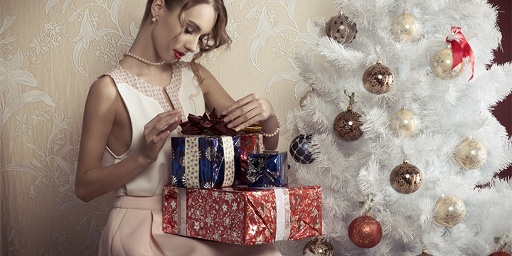 elegant woman next to Christmas tree with gifts