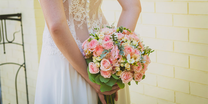 Bride in lace back dress holding bouquet behind back