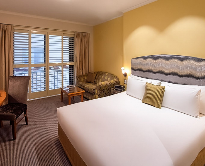 Internal view of a standard yellow guestroom with white bed